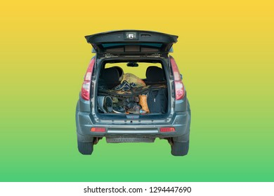 isolated opened car trunk with luggage on yellow background
