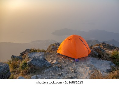 isolated orange camping tent near cliff on lantau peak, Hong Kong in sunrise and fog with copy space