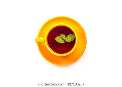 Isolated orange cup and saucer with lemon and mint leaf top view on a white background.