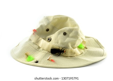 An isolated over white image of a fishermans hat with fly lures.