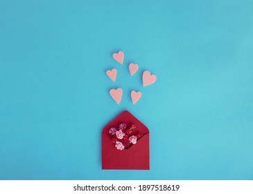 Isolated paper envelope with red roses and fly hearts over a blue background with copy space