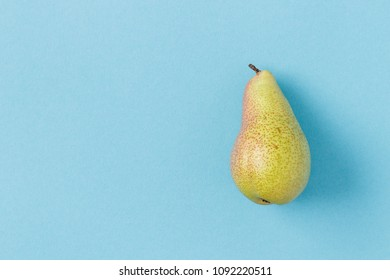 An isolated pear shot from above on a pastel blue background. There is empty space on the left.