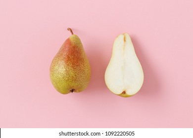 Isolated pears shot from above on a pastel pink background. One pear is whole and the other one is halved.