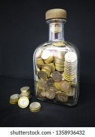 Isolated photo of a bottle with coins on a dark background. Coins Kazakhstan tenge in a bottle on a dark background. Kazakh money. Coins of tenge.