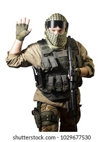 Isolated photo of a fully equipped military soldier standing with rifle and tactical glasses showing military hand sign.