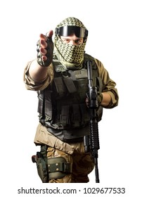 Isolated photo of a fully equipped military soldier standing with rifle and tactical glasses showing military hand sign towards camera.