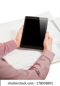 Isolated photo of men hands holding tablet with reflection on screen on table with blueprints