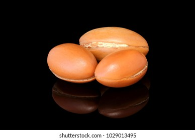 Isolated photo of some argan nuts reflected with black background.