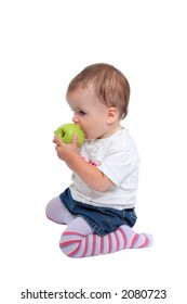 Isolated photo of young, cute baby girl with brown hair kneeling down eating fresh green apple or fruit wearing stripy tights