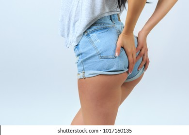 An isolated photo of a young woman's lower body with both hands on her butt