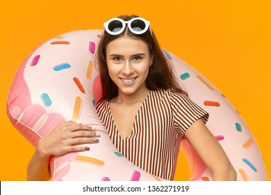 Isolated picture of cheerful overjoyed young European female with tanned sking and happy carefree smile posing at orange wall with round sunglasses on her head, carrying inflatable pink swimming ring