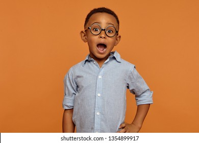 Isolated picture of handsome emotional bug eyed dark skinned schoolboy wearing stylish glasses expressing shock, keeping mouth wide opened. Excitement, fascination and true genuine emotions