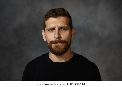 Isolated picture of handsome frustrated young male with thick beard and mustache frowning, biting lips and looking down with guilty facial expression, feeling ashamed and upset or being sorry