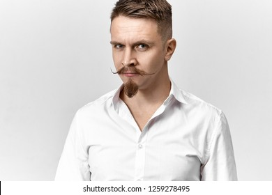 Isolated picture of handsome successful young male entrepreneur with handlebar mustache and goatee beard posing in studio wearing white formal shirt, looking at camera with confident smile