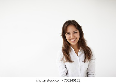Isolated picture of natural positive young woman employee of mixed race appearance dressed in white blouse, looking at camera with pleased joyful smile, happy after she got promotion at work.