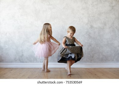 d14f9a97abc Isolated picture of two little girls siblings standing barefooted on wooden  floor at home and rejoicing. Three kids sitting in a ...