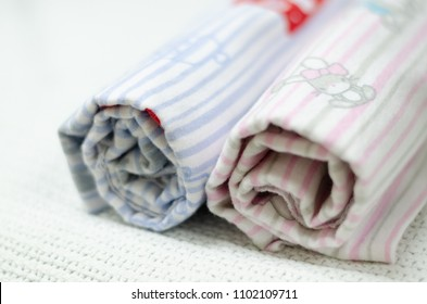 An isolated pink and blue baby receiving blanket rolled up, lying side by side
