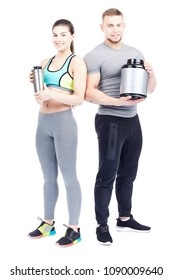 Isolated portrait of athletic man and woman holding container with sports nutrition and shaker bottle