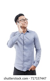 Isolated portrait of a cheerful Asian businessman wearing a blue shirt, jeans and glasses and talking on his smartphone.