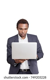 Isolated portrait of a concentrated young African American businessman wearing a suit and looking attentively at his white laptop screen. Mock up