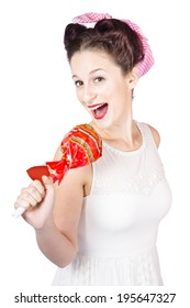 Isolated portrait of a funny pin-up sing star talking into large lollypop microphone. Pop star karaoke