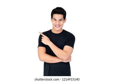 Isolated portrait of  happy smiling Asian man wearing casual black t-shirt pointing hand to empty space aside studio shot white background