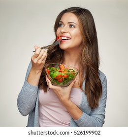 isolated portrait of happy woman eating green salad with glass dish
