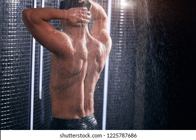 Isolated portrait of healthy muscular tan-skinned man with perfect athletic body taking shower over black background. Handsome young caucasian male enjoying running water drops.