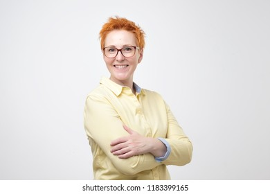 Isolated portrait of smiling mature woman with interesting short redhair standing with crossed arms. Positive facial emotion