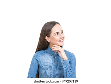 Isolated portrait of a smiling young woman with long dark hair wearing a jeans shirt and looking sideways.