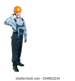 Isolated. Portrait of a worker with overalls and a protective helmet. A cheerful man in overalls receives phone calls.