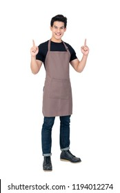 Isolated portrait of a young attractive male asian barista in brown apron smiling and  pointing hand upward