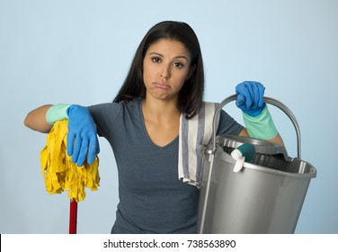isolated portrait of young beautiful unhappy and frustrated housekeeping woman holding mop and wash bucket as hotel cleaner service or house maid looking tired and overworked