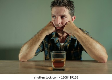 isolated portrait of young drunk addict and alcoholic man drinking whiskey glass intoxicated looking wasted resisting temptation to his alcohol addiction and abuse problem in alcoholism concept