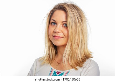 Isolated portrait of a young girl in a white embroidered blouse. Beautiful blonde in a closed pose. Lovely girl with blond hair.