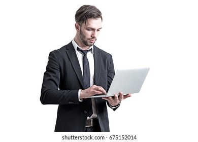 Isolated portrait of a young and handsome bearded businessman in a suit holding a laptop and working. Concept of success.