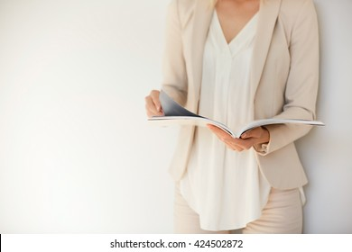 Isolated portrait of young stylish woman wearing formal suit, reading fashion magazine and looking for information on trends, during short break in the office. Lifestyle concept. Selective focus