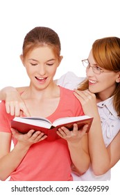 isolated portrait of young woman pointing at the book and her friend looking surprised