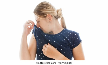 Isolated portrait of young woman smelling her t-shirt