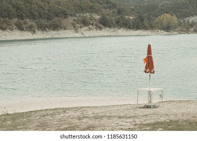 Isolated red beach umbrella on the shore of Fiastra Lake, Marche, Italy, Europe