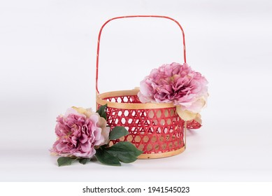 Isolated red Chinese style rattan basket with pink flower decoration on white background
