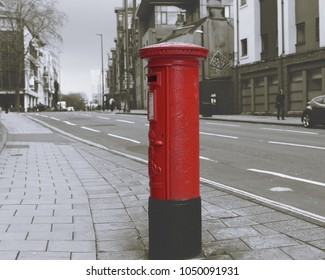 Isolated Red English Post Box on a street, black and white split toning background, shallow depth of field horizontal photography