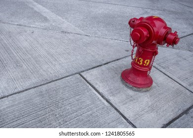 isolated red fire hydrant on concrete with square and angled shapes in a cantered frame