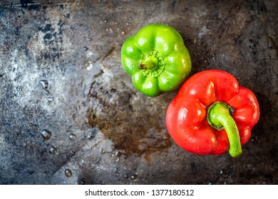isolated red and green peppers on wet dark metal background flat lay