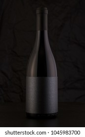 Isolated Red Wine Bottle in a Black Background, fresh and Clean with Black Capsule and Black Label