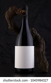 Isolated Red Wine Bottle in a Black Background, fresh and Clean with Black Capsule, White Label and Vine