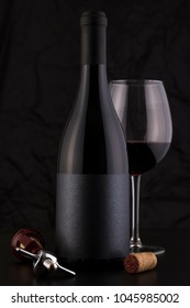 Isolated Red Wine Bottle in a Black Background, fresh and Clean with Black Capsule, Glass and Black Label