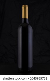 Isolated Red Wine Bottle in a Black Background, fresh and Clean with Gold Capsule