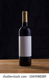 Isolated Red Wine Bottle in a Black Background, fresh and Clean with Gold Capsule, White Label and Glass Vine