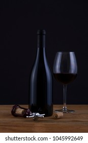 Isolated Red Wine Bottle in a Black Background, fresh and Clean with Black Capsule with Black Label and Glass
